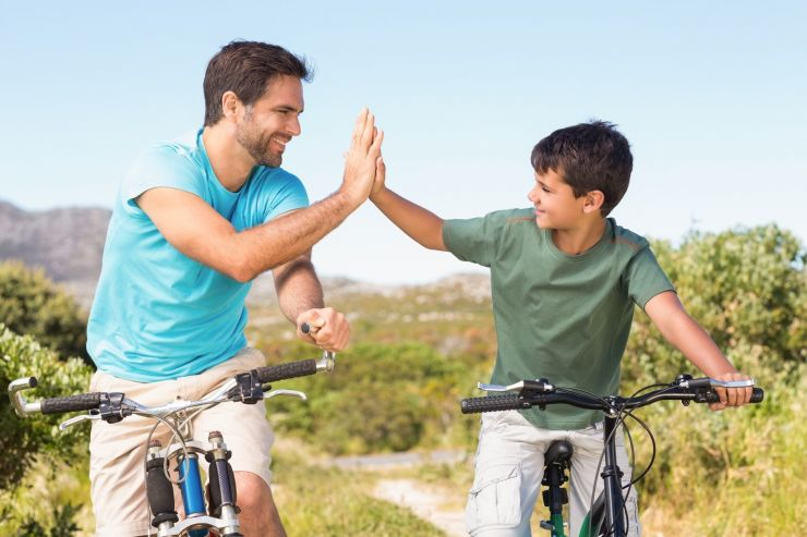 father son bikes highfive